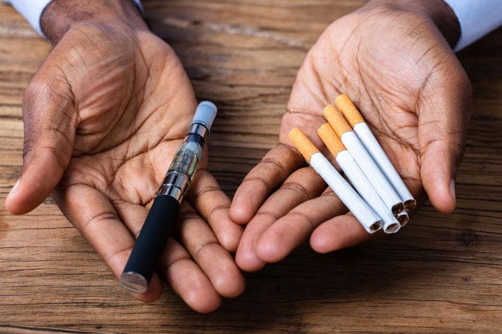 hombre sujetando un vapeador tipo lápiz y cigarrillos