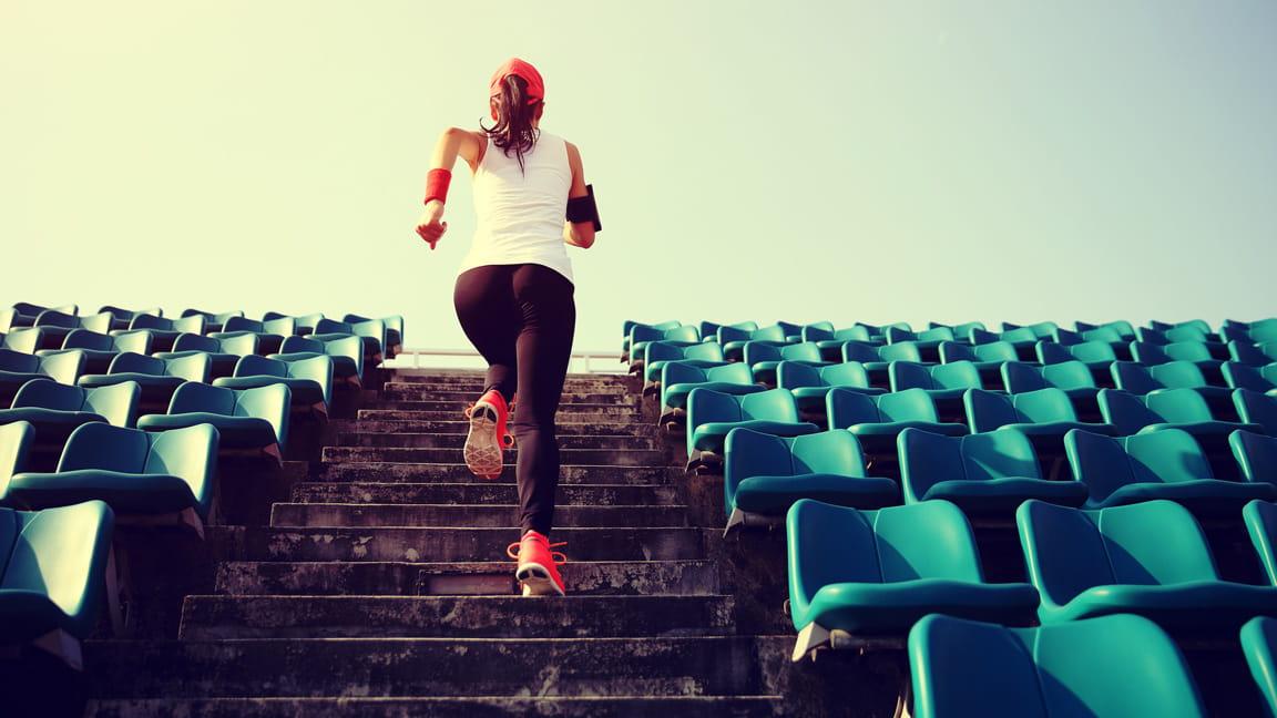mujer corriendo por las escaleras de un estadio
