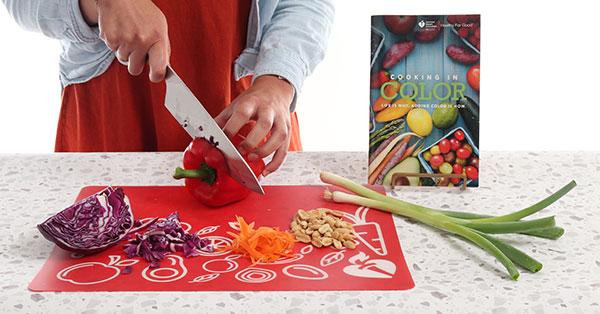 Primer plano de unas manos cortando verduras en la tabla de cortar con el libro de cocina de la American Heart Association Cooking a color