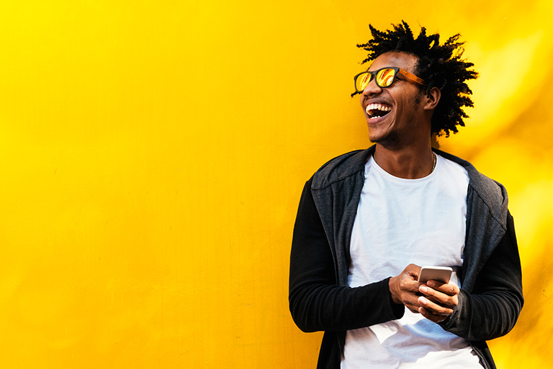 happy Black man wearing sunglasses using cell phone in front of bright yellow wall