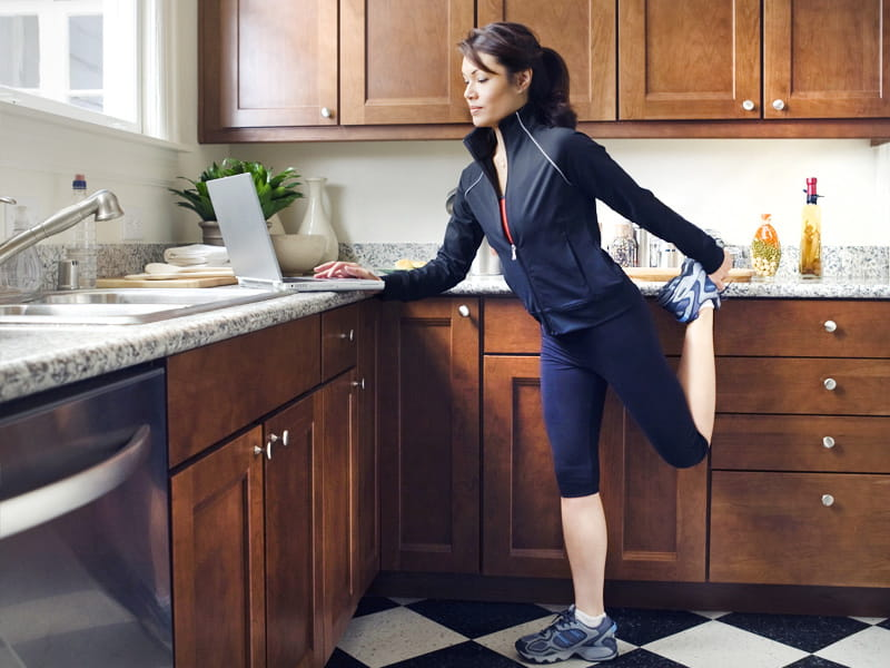 busy woman works on laptop in kitchen while exercising