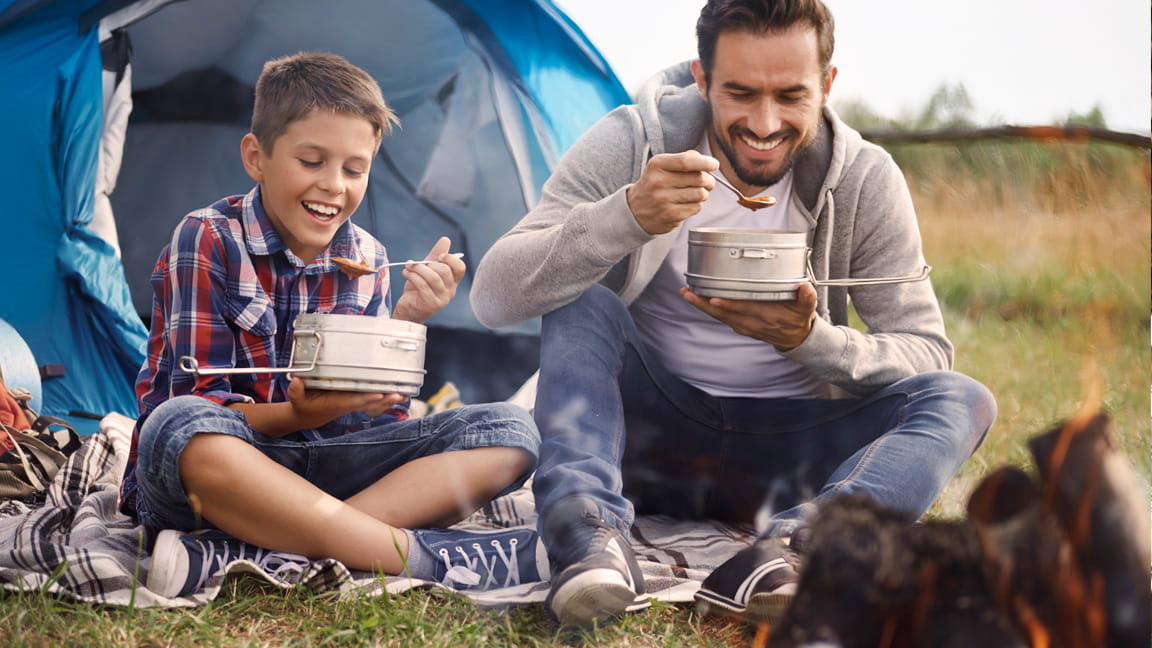 father and son eating at campfire