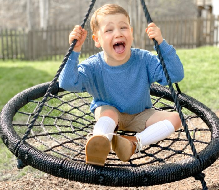 Heart Hero Finn Blumenthal laughing on a swing