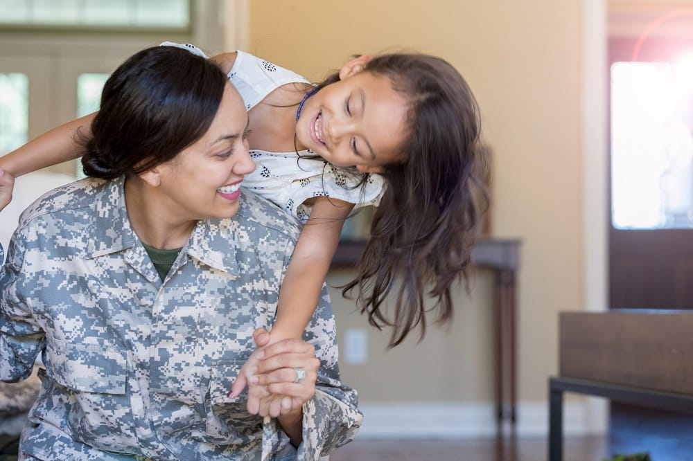 Young Hispanic woman in the military with young girl smiling