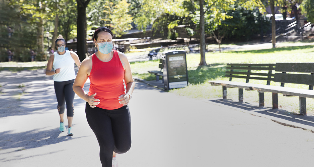 woman running outdoors wearing mask
