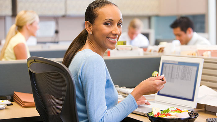business woman eating lunch at her desk while working