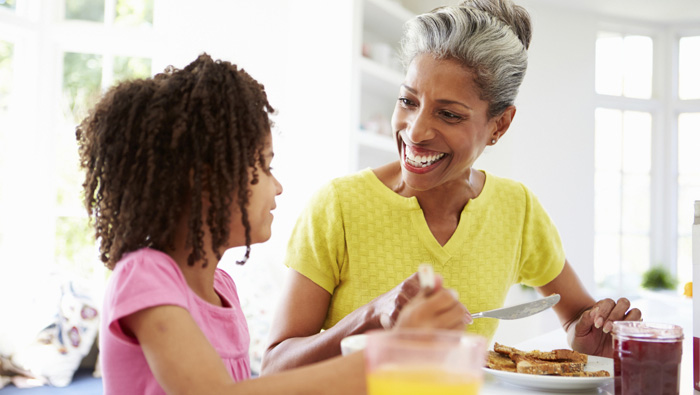 grandmother and granddaughter eating breakfast at the kitchen table