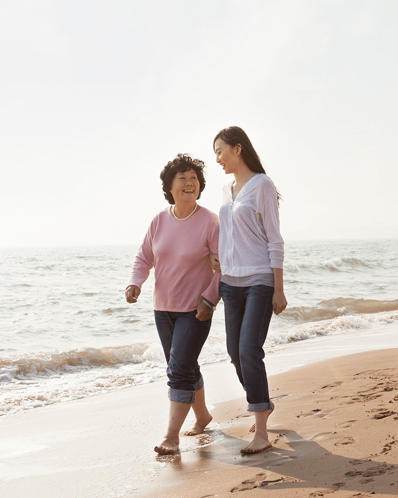 two women, probably a mother and daughter, walking on a beach