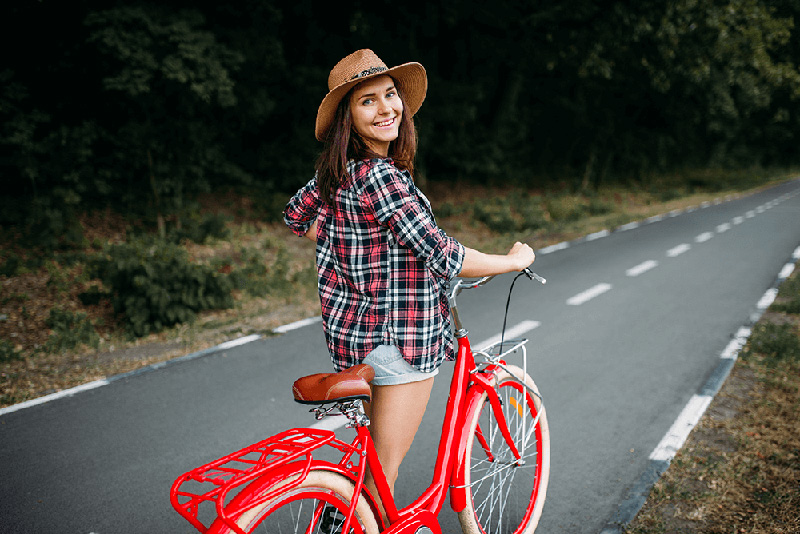 young woman walking red vintage bicycle down a tree-lined street