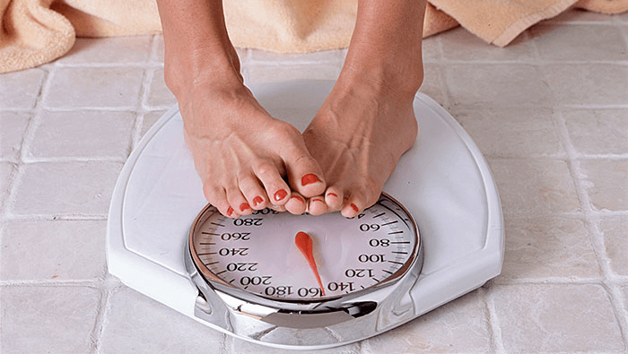 close up of woman's feet standing on a scale
