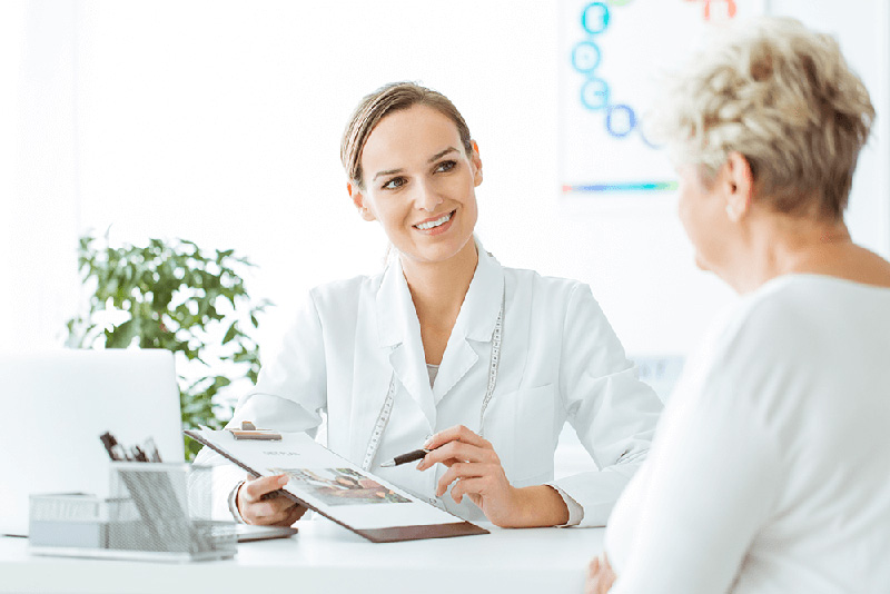 smiling female doctor discussing notes with woman patient