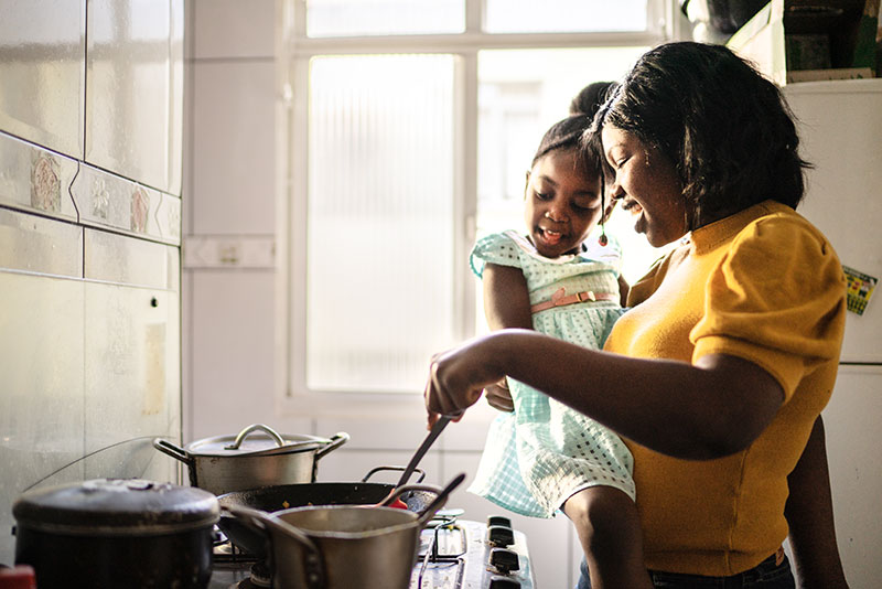 Mom holding daughter cooking