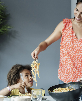 Mom serving child spaghetti