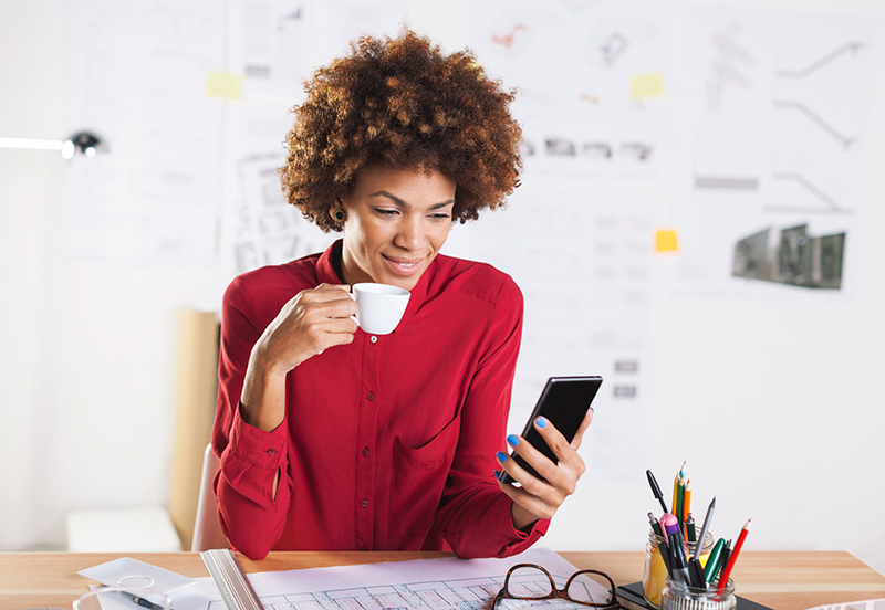 young woman drinking at desk using mobile phone