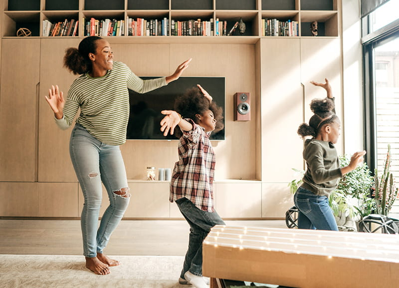 mom dancing with daughters at home