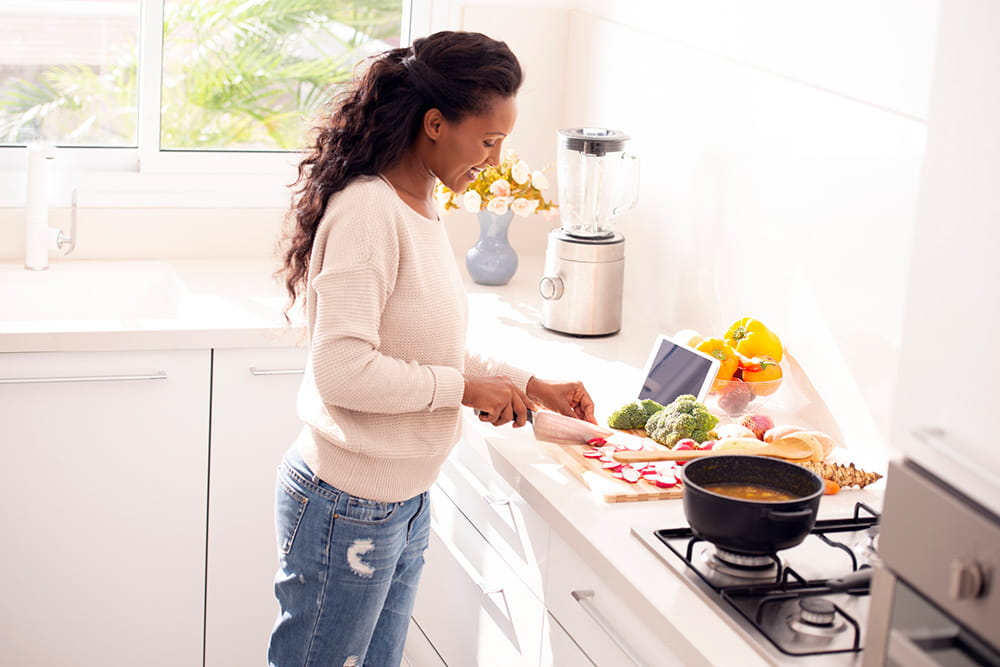 woman chopping food to put in pot on stove