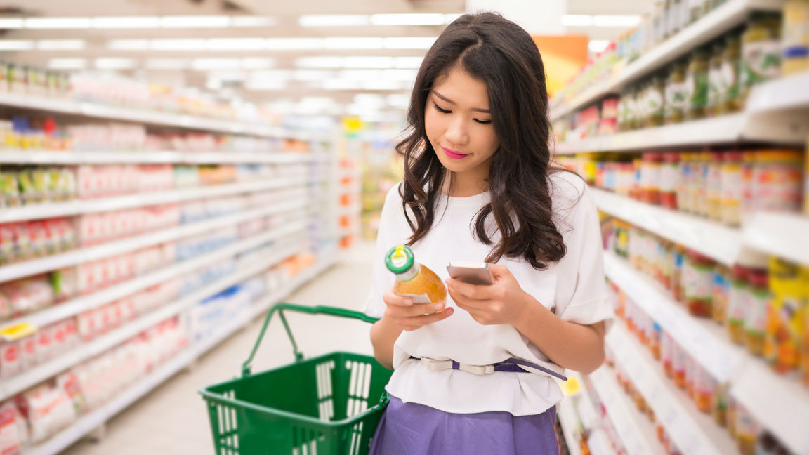 Asian Woman looking up ingredients on label using mobile phone