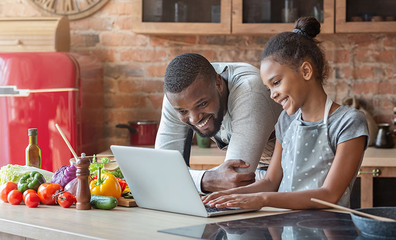 Dad and daughter read recipe on tablet while cooking