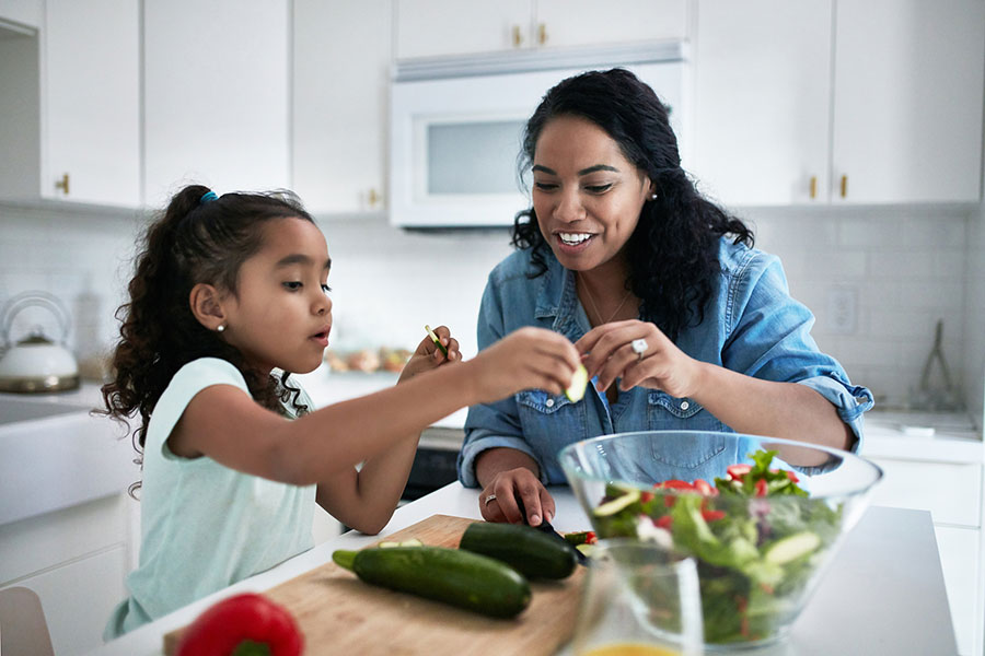 Mom and daughter make salad in kitchen