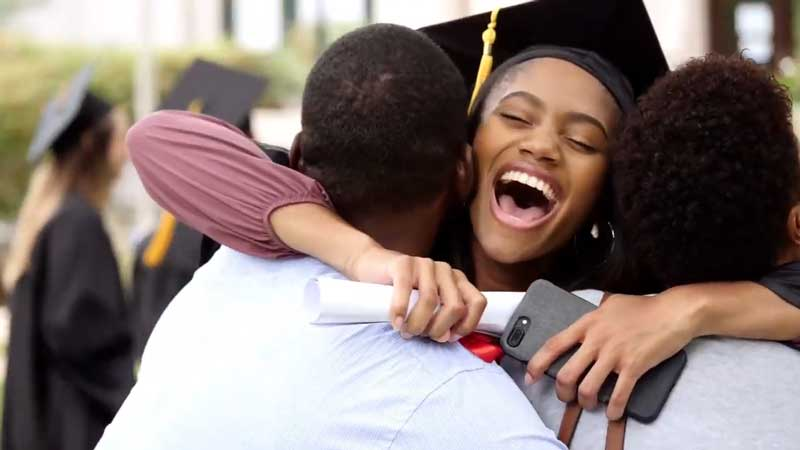 Still from COVID 19 Vaccine video of graduate hugging parents