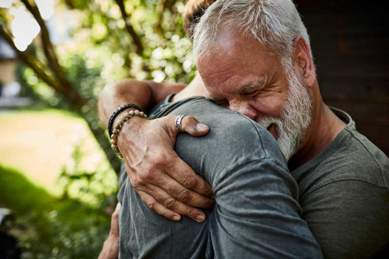 older man hugging son