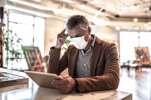 man wearing face mask while reading tablet