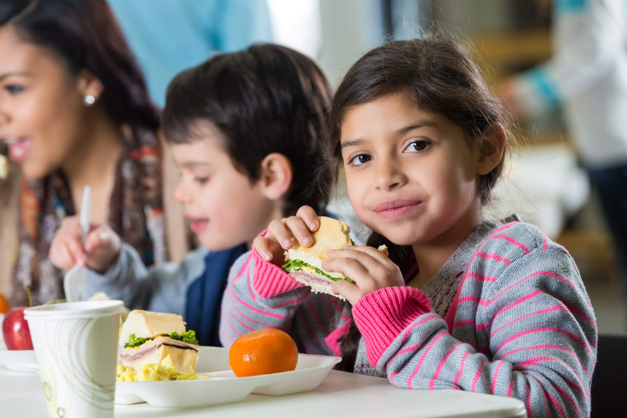 Young girl eating sandwich at school cafeteria lunch table
