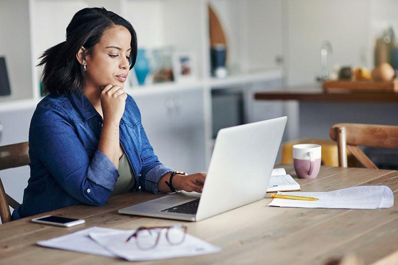 mujer leyendo en una computadora portátil
