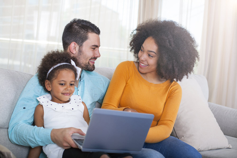 Mom and dad on laptop with young daughter