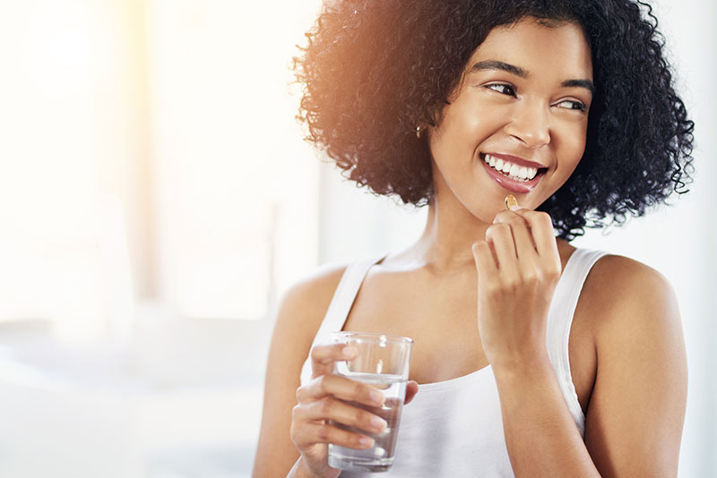 happy woman taking pill with water