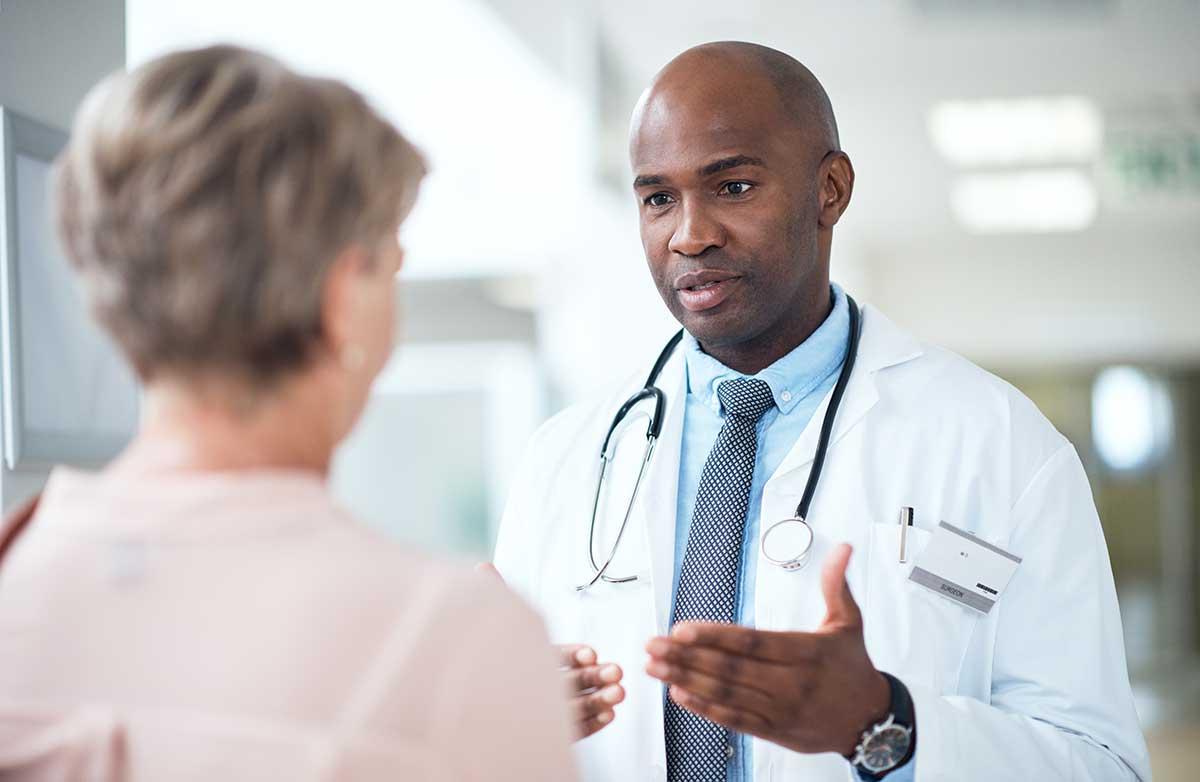 african american doctor speaking with female patient