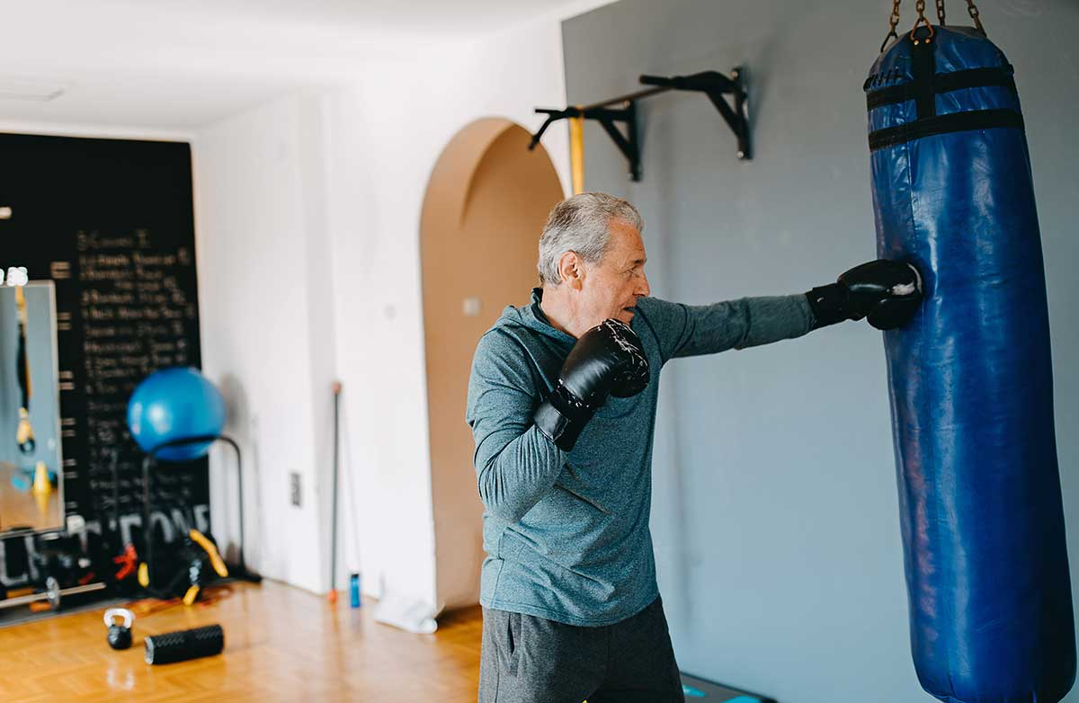 middle aged man punching a punching bag