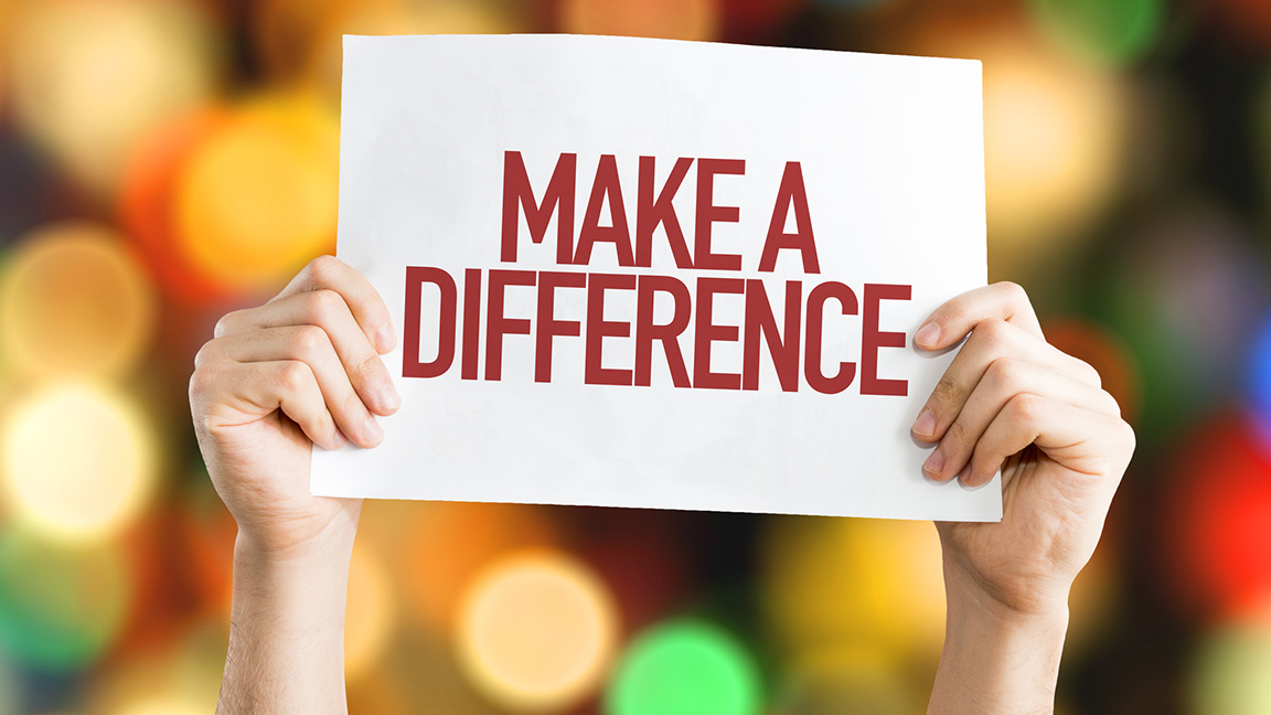 Manos sujetando una señal que dice Make A Difference