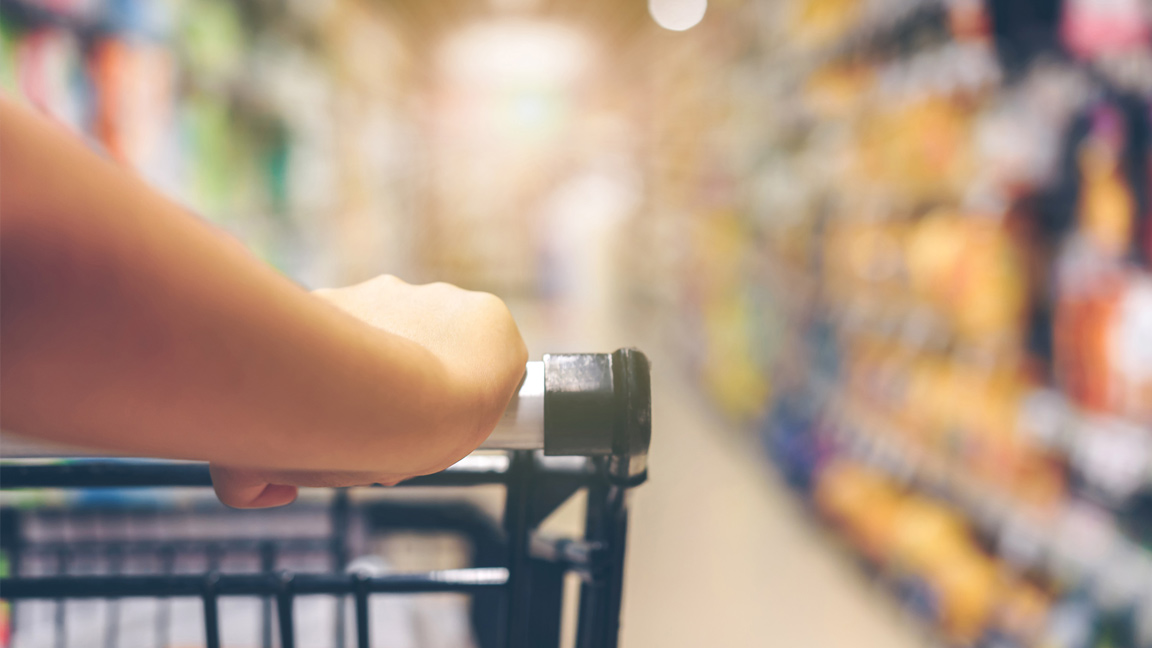 close up of arm pushing cart in isle of grocery store