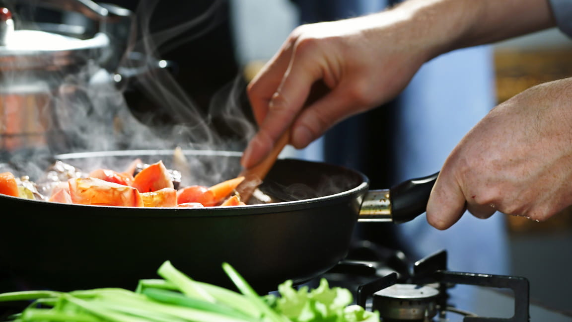 close up of hands sauteing food over store