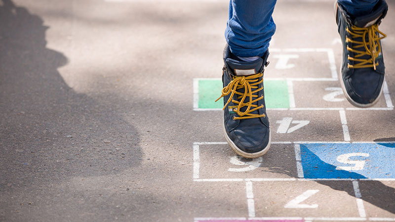 Close-up of a Child's feet playing hop scotch outdoors