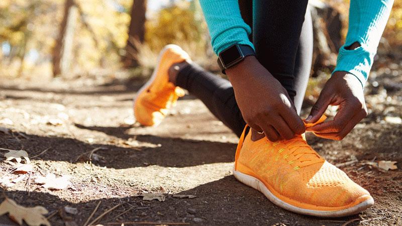Female African American runner tying sneaker
