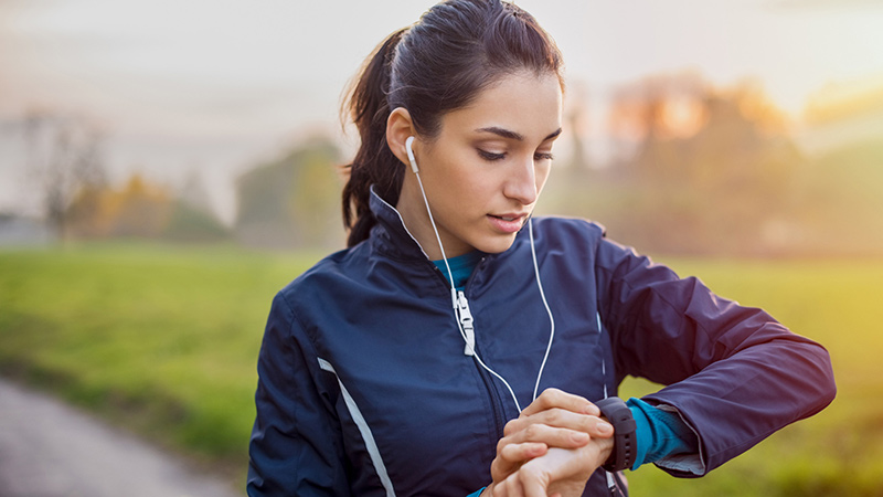 Woman outdoors working out looking at watch