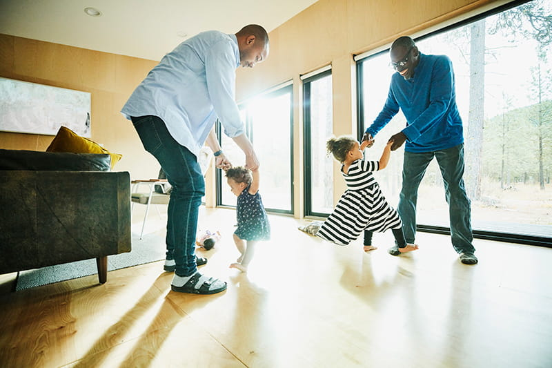 Grandfather father dancing with daughters at home