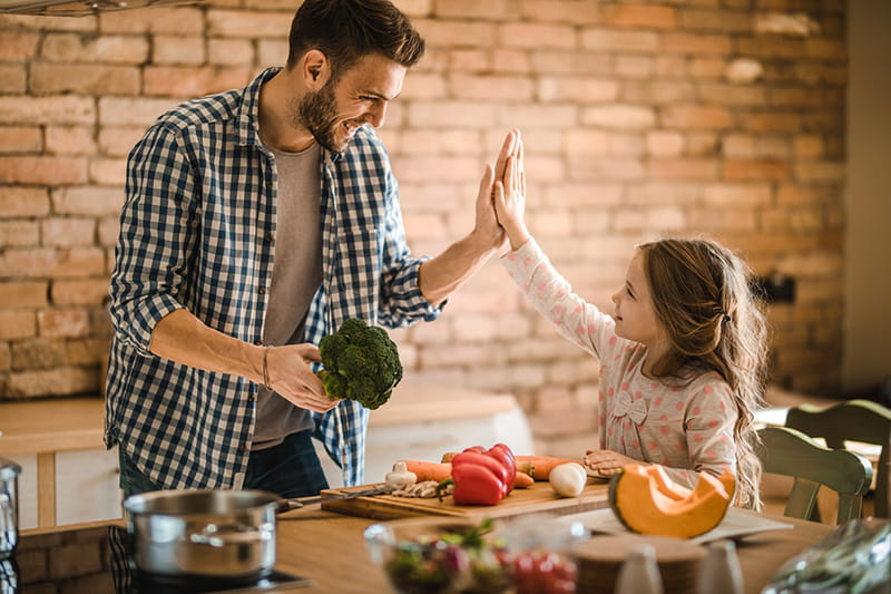 father holding broccoli high-five daughter