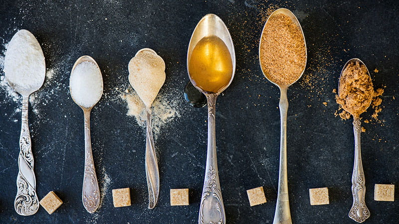 spoonfuls of different kinds of sugar sweeteners