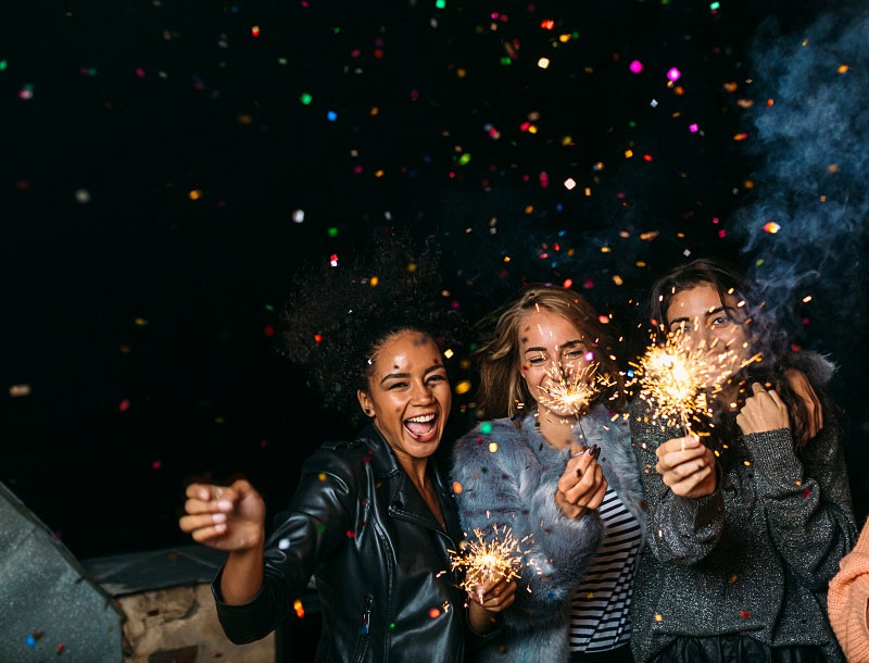 group of girls laughing while holding sparkler fireworks