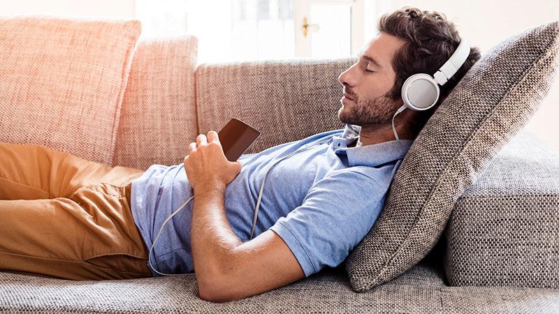 Hombre en el sofá escuchando música con unos auriculares