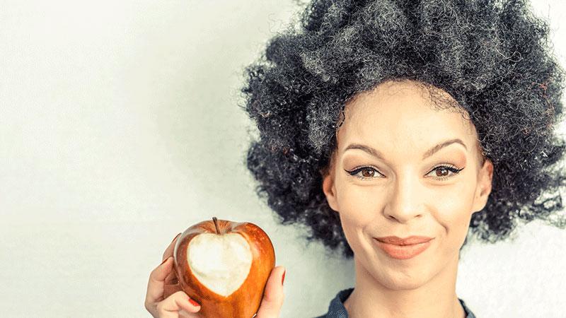 mujer de pelo gris comiendo una manzana mordida en forma de corazón