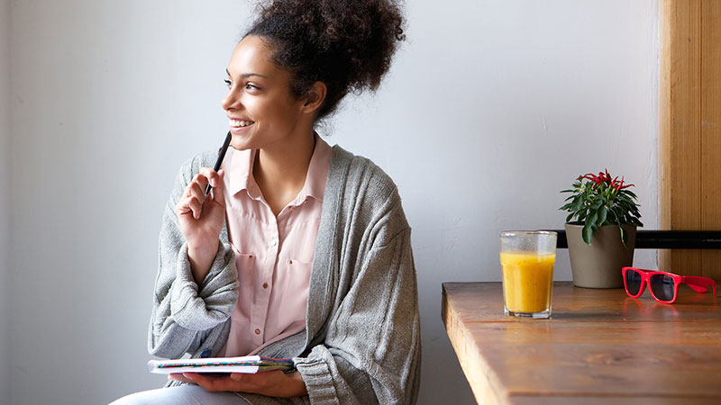 smiling African American woman writing in journal in pajamas