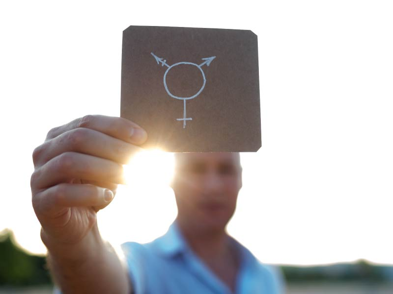 Person holding transgender symbol. (ljubaphoto, Getty Images)